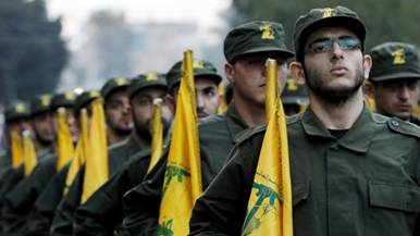 Hezbollah fighters hold party flags during a parade in a southern suburb of Beirut, Lebanon. (photo credit: AP/Hussein Malla/File)