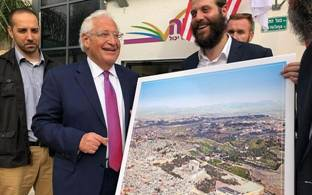 US Ambassador to Israel David Friedman is pictured next to a man holding a poster of the Jewish Temple replacing the Muslim Dome on the Rock on Jerusalem's Temple Mount, at an event for the Achiya educational nonprofit in Bnei Brak, May 22, 2018. (Courtesy: Kikar HaShabbat)